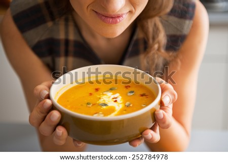Closeup on young woman enjoying pumpkin soup - stock photo