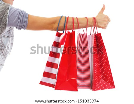 Closeup on young woman hand with christmas shopping bags showing thumbs up - stock photo