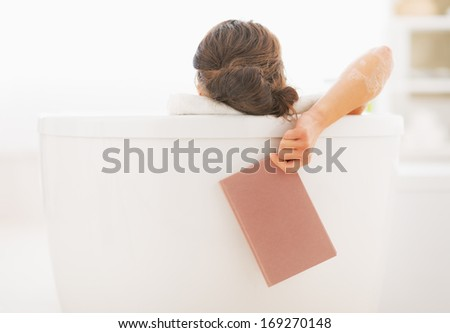 Closeup on young woman in bathtub holding book