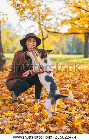 Closeup on young woman playing with dog outdoors in autumn - stock photo