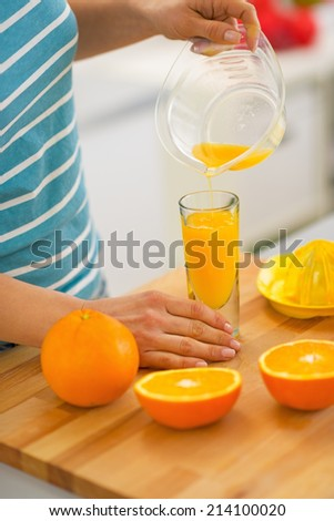 Closeup on young woman pouring fresh orange juice in glass - stock photo