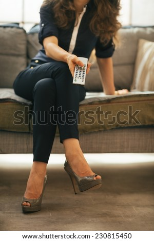 Closeup on young woman watching tv in loft apartment - stock photo