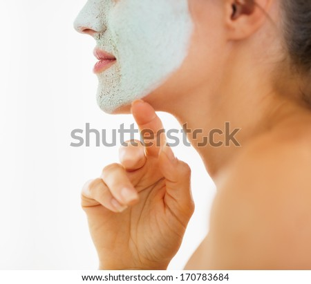 Closeup on young woman with cosmetic mask on face