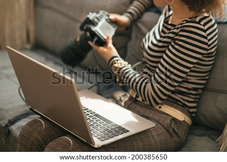 Closeup on young woman with laptop using modern dslr photo camera - stock photo