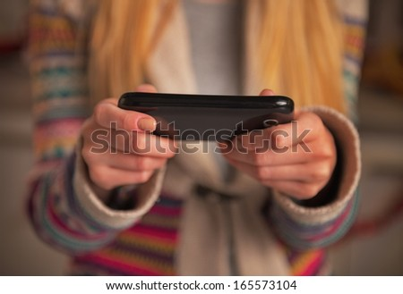 Closeup on young woman writing sms - stock photo