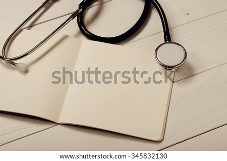 Closeup open notebook with blank pages with stethoscope on a white doctor's table. Top view. Free space for text. Copy space - stock photo