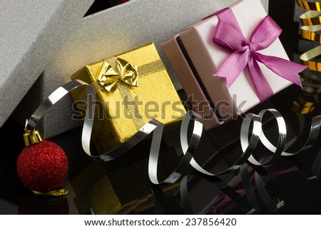 closeup opened big silver box,  little  glamour gold and pink gift boxes with bright christmas red ball on dark reflection surface  - stock photo