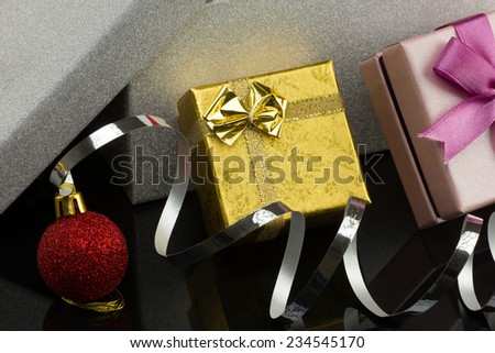 closeup opened big silver box, two little  glamour gift boxes with bright christmas red ball on dark reflection surface - stock photo