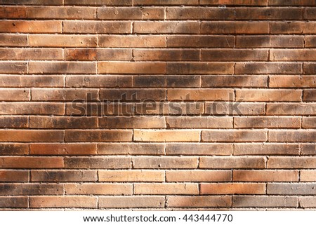 Closeup orange brick wall texture with shadow for background. Grunge retro vintage of brick wall. Part of old brick wall for design with copy space for text or image. - stock photo