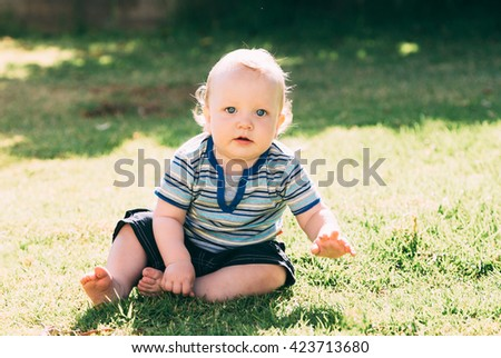 Closeup outdoor portrait of a cute sitting   baby boy - stock photo