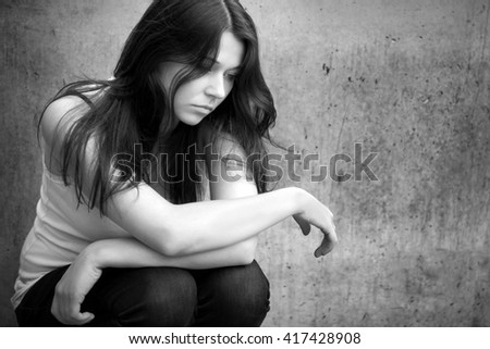 Closeup outdoor portrait of a sad teenage girl looking thoughtful about troubles in front of a gray wall, black and white photo - stock photo