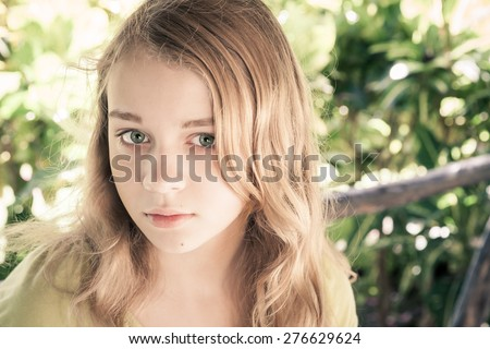 Closeup outdoor portrait of beautiful blond Caucasian teenage girl in a park with natural light, vintage toned photo filter effect, instagram style - stock photo