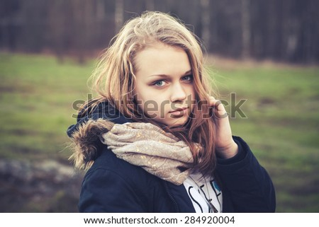 Closeup outdoor portrait of beautiful blond Caucasian teenage girl in a spring forest, tonal photo filter effect, old instagram style  - stock photo