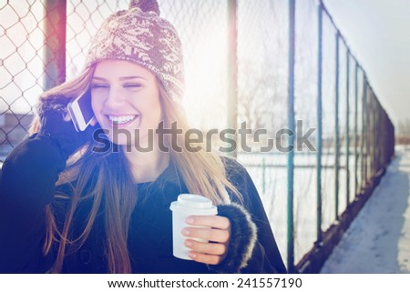 Closeup outdoor portrait of cute happy blonde Caucasian teenage girl with takeaway coffee talking on smartphone. Young woman with long hair with coat, gloves, knitted hat outdoors in winter by fence. - stock photo