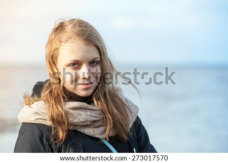 Closeup outdoor portrait of smiling beautiful blond Caucasian teenage girl on a Sea coast - stock photo
