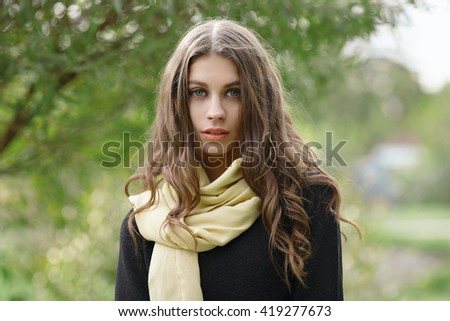 Closeup outdoor portrait of young beautiful brunette woman with wavy long hair looking into camera posing against forest park background