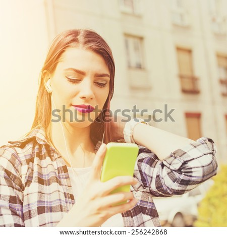 Closeup outdoors portrait of beautiful millennial teenage girl with smartphone texting outdoors in summer. Young woman with cellphone and earphones, urban background, filter, retouched, square format. - stock photo