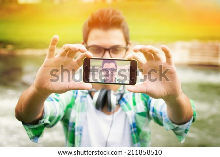 Closeup outdoors shot of young hipster man with headphones taking a selfie with smart phone by the river. Modern teenage guy taking a self portrait outdoors. - stock photo