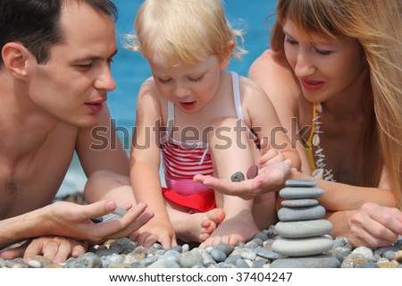 closeup parents with child on sea coast and  pyramid of stones - stock photo