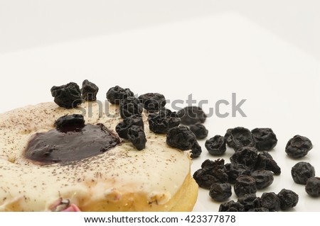 Closeup partial view on a ring shaped doughnut, fried and glazed with icing, topped with cinnamon powder sprinkles and blueberry jam. Garnished with dried blueberries. Isolated on white background. - stock photo