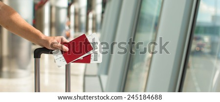 Closeup passports and boarding pass at airport indoor - stock photo