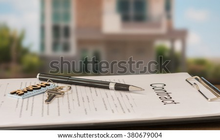closeup pen on contract document with house key in house background. - stock photo
