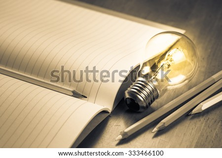 Closeup pencil on opened notebook with glowing light bulb, creative writing concept - stock photo