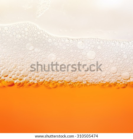 Closeup photo bubbles of beer froth in glass - stock photo