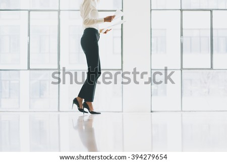 Closeup photo business woman wearing modern suit. Open space loft office. Holding papers hands. Analyze plans, meeting, panoramic windows background. Horizontal mockup.
