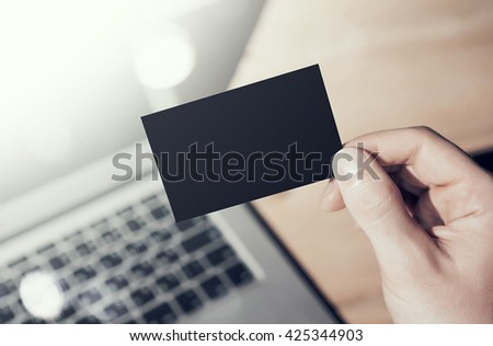 Closeup Photo Man Showing Blank Black Business Card and Using  Modern Laptop on Wood table Blurred Background. Mockup Ready for Private Information. Sunlight Flares Gadget. Horizontal mock up
