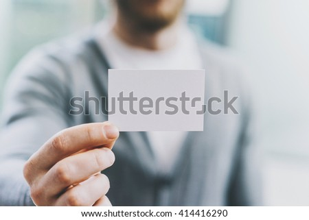 Closeup photo man wearing casual shirt and showing blank white business card. Blurred background. Ready for private information. Horizontal mockup - stock photo