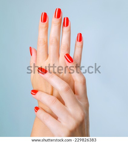 Closeup photo of a beautiful female hands with red long natural nails, manicure
