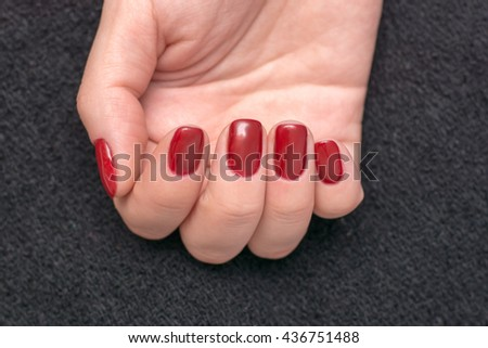 Closeup photo of a beautiful female hands with red nails - stock photo