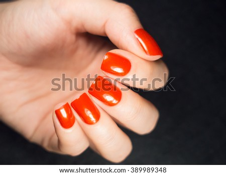 Closeup photo of a beautiful female hands with red nails isolated on black background
