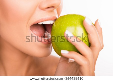 Closeup photo of a beautiful healthy girl biting an apple - stock photo
