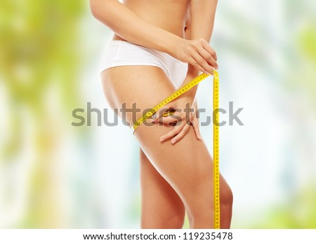 Closeup photo of a Caucasian woman's leg. She is measuring her thigh with a yellow metric tape measure after a diet - stock photo