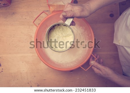 Closeup photo of a chef lady sifting flour for kneading. Retro colors, directly above