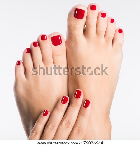 Closeup photo of a female feet with beautiful red pedicure over white background - stock photo