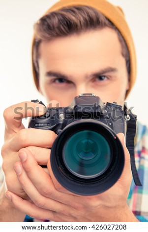 Closeup photo of a photographer with hat taking a photo - stock photo