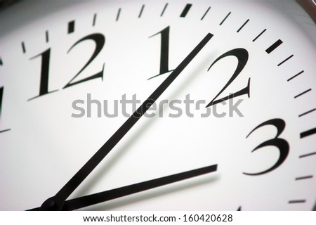 Closeup photo of a round black and white clock. Simple scale with minutes, hours and seconds.