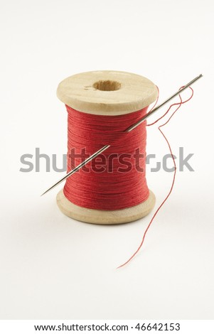 Closeup photo of a spool with red thread and a needle, photographed against a light background for isolation - stock photo