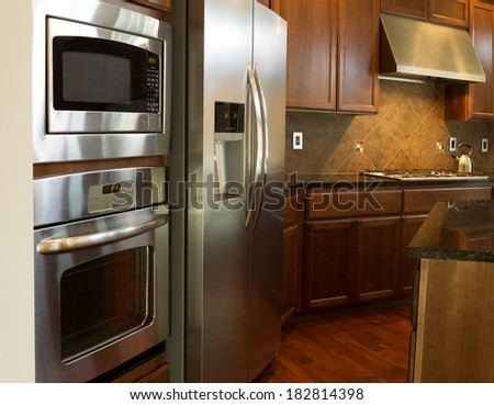 Closeup photo of a stainless steel appliances in modern residential kitchen with stone counter tops and cherry wood cabinets with hardwood floors  - stock photo
