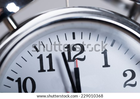 Closeup photo of alarmclock. Almost noon time - stock photo
