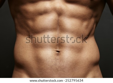 Closeup photo of an athlete with perfect abs - stock photo