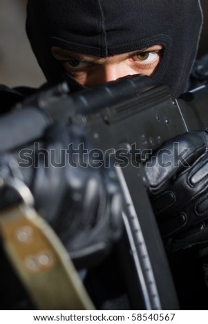Closeup photo of armed man in black mask - stock photo