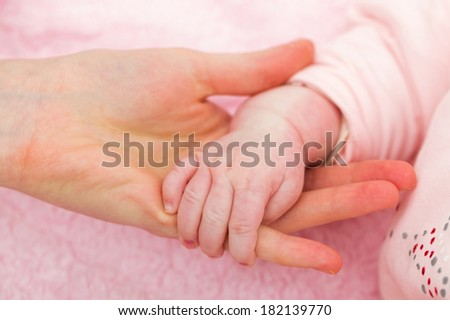 Closeup photo of baby and mother hands - stock photo
