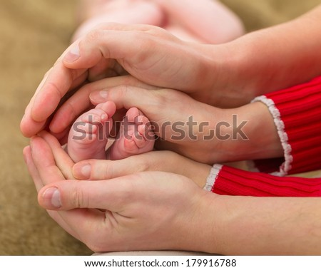 Closeup photo of baby foots in parents hands - stock photo
