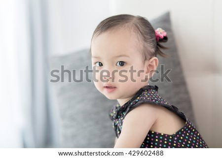 Closeup photo of beautiful cute asian baby's expression at home.  Selective focus - stock photo