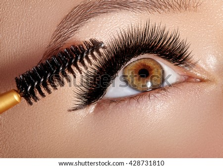 Closeup photo of beautiful female eye with extreme long lash. Mascara applying closeup. Black mascara brush. Eyes make-up apply. Sexy eyelashes makeup.  - stock photo