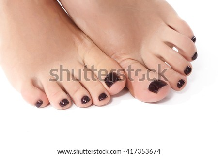 Closeup photo of beautiful female feet with dark pedicure. Clean soft skin, healthy nails with gel polish, beauty of woman's legs. - stock photo